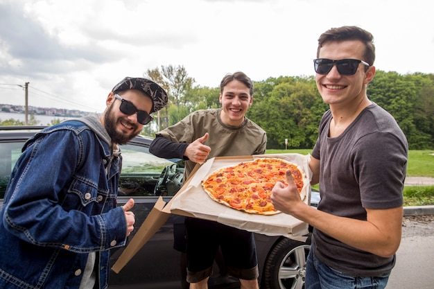 Company of young guys with pizza doing excellent sign in nature