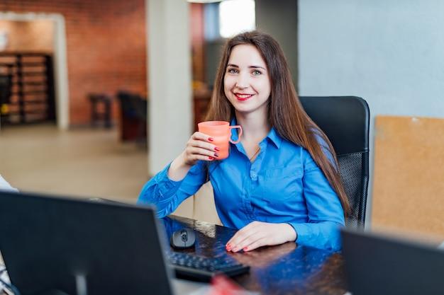 ピンクのカップを持つコンピューターの前でcompanyficeに座っている若い女性プログラマー。カメラ目線と笑顔のプロのコンピューターエンジニア。ソフトウェアの仕事