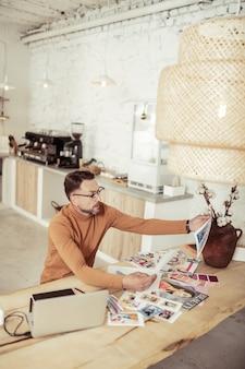 사진 비교. 집중된 패션 디자이너가 테이블에 앉아 그의 드레스와 함께 사진을보고 있습니다.