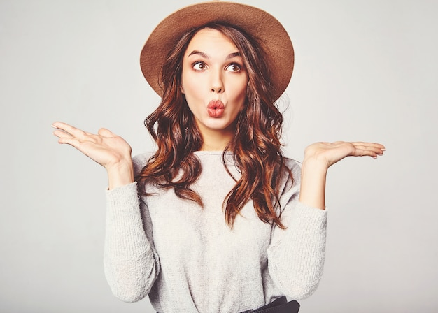 Comparison concept. young brunette woman in casual clothes and brown hat