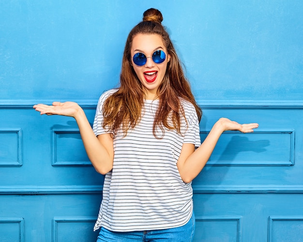 Comparison concept. young brunette woman in casual summer hipster clothes displaying something on both flat hands for similar choice of product, posing near blue wall