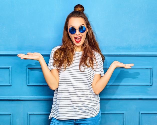比較のコンセプト。青い壁に近いポーズ、製品の同様の選択のための両方の平らな手に何かを表示するカジュアルな夏流行に敏感な服の若いブルネットの女性