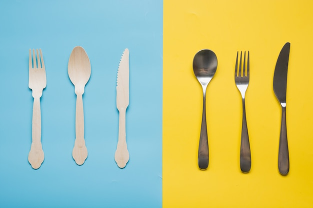 Comparison of reusable metal cutlery, and eco wooden sopoon, knife. view from above. top view. flat lay.