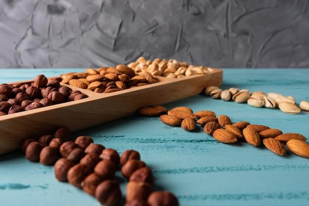 青い木製のテーブルにナッツが入ったコンパートメントディッシュ。カシューナッツ、ヘーゼルナッツ、アーモンド。