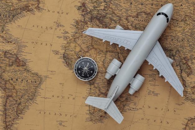 Compass and air plane on old map. travel, adventure concept