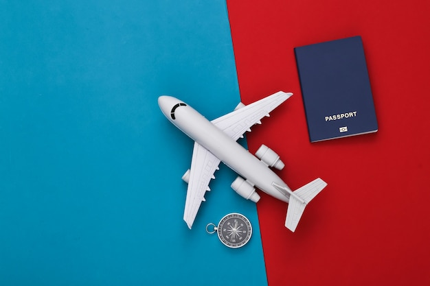 Compass and air plane, passport on red-blue