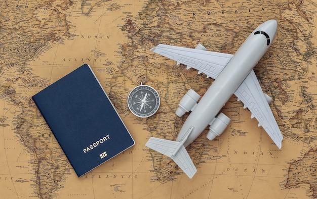 コンパスと飛行機、古い地図のパスポート。旅行、冒険の概念