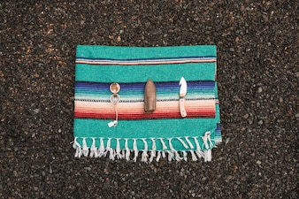 Compass and knife on bright blanket