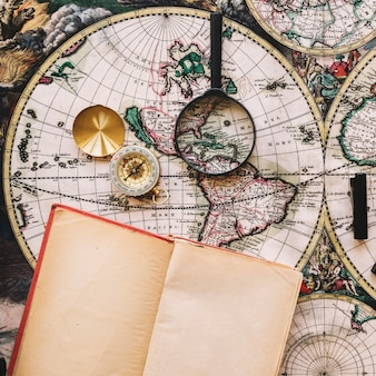 Compass and magnifying glass near opened notebook