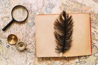 Compass and magnifying glass near retro notebook
