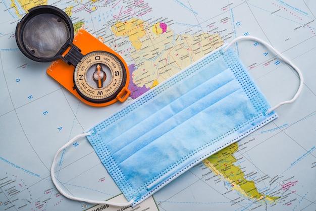 世界地図上のコンパスと医療マスク。安全な旅行のコンセプト