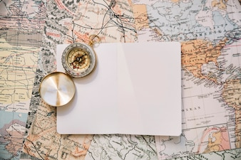 Compass and paper on map