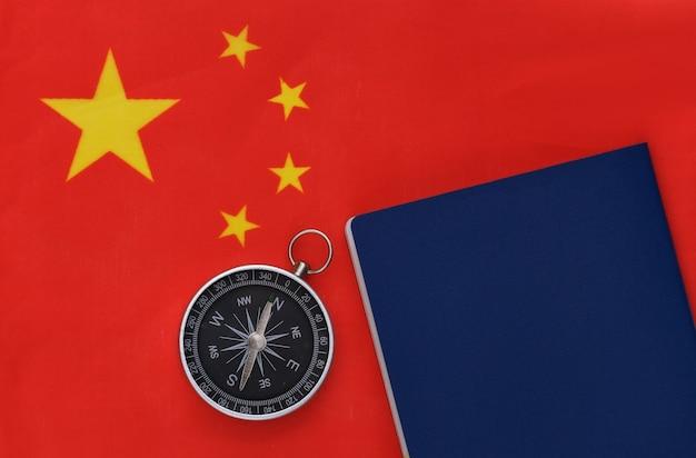 Компас и паспорт на флаге китая крупным планом. вид сверху