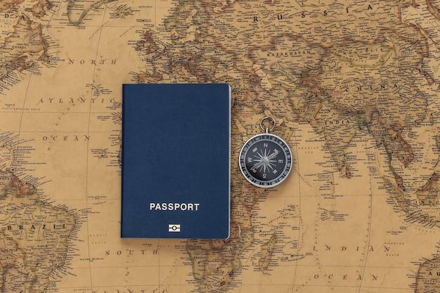 古い地図上のコンパスとパスポート。旅行、冒険の概念
