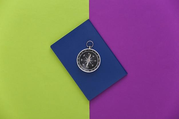 보라색 녹색 배경에 나침반과 여권입니다. 평면도. 미니멀리즘 여행 컨셉입니다. 플랫 레이