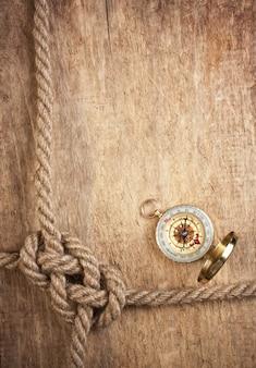 Компас и веревочный узел на деревянном пространстве