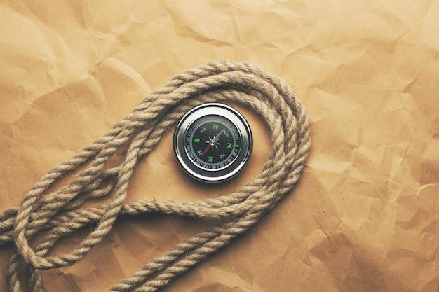 Компас и веревка на коричневой бумаге