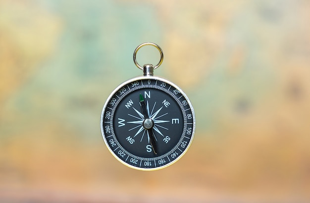 Compass on a blurred background of an old map