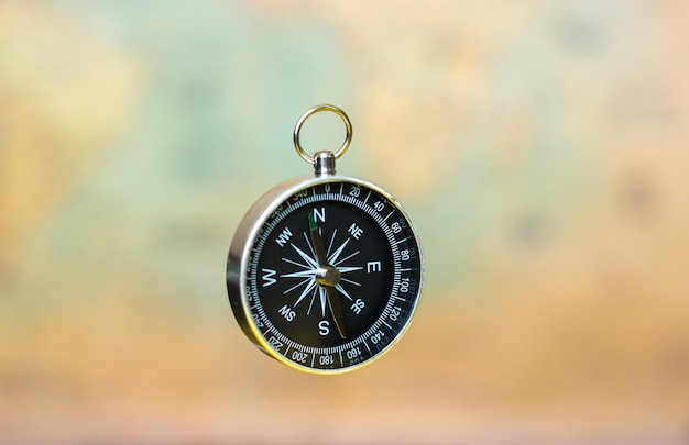 Compass on a blurry background with a vintage world map