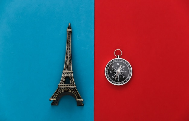 Compass and eiffel tower figurine on red-blue