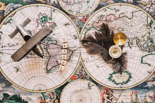 Compass and feathers near travel writing and plane