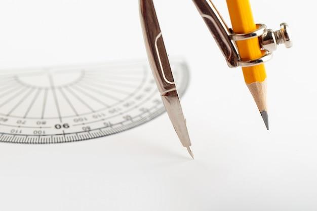白い机の上の鉛筆で分離された描画と製図のためのコンパス