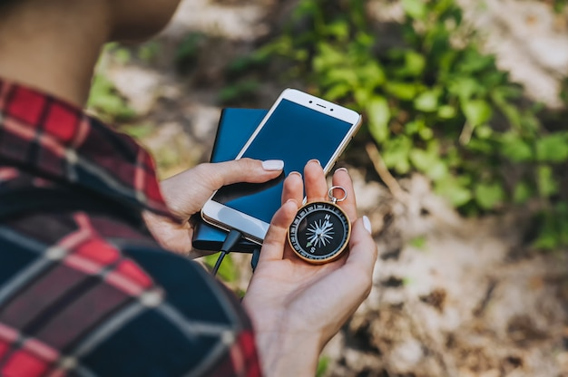 Compass in a girl s hand with a smartphone and a power bank. against the grass and sand.