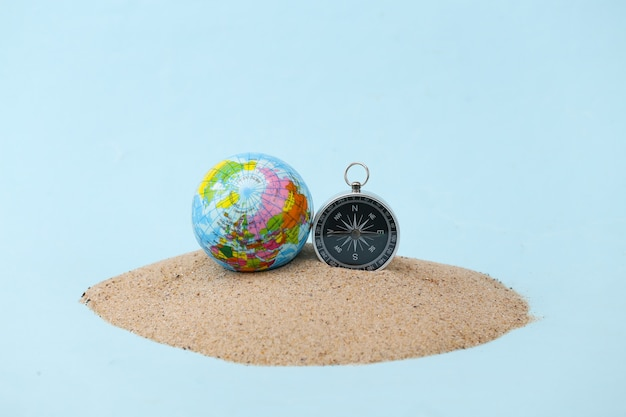 Compass and globe on an islet of sand. travel, adventure concept