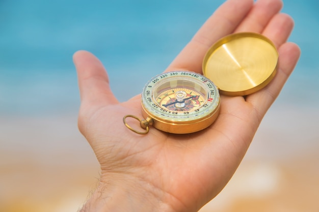 Compass on hand in the sea and the beach.