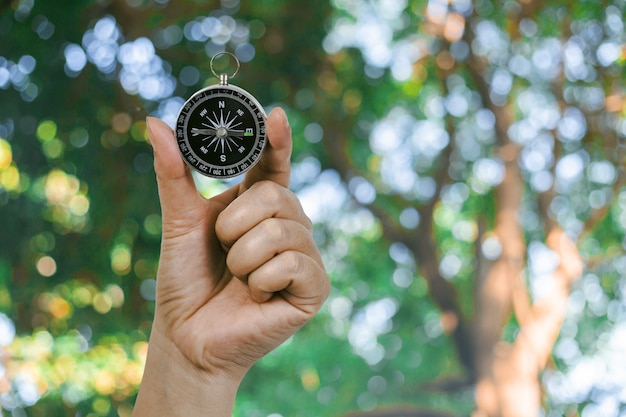 Compass in hand with nature background