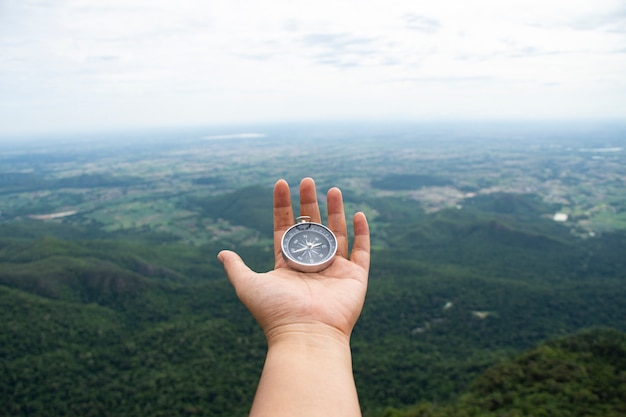 Compass hand with view of forest, trekking and lost in forest concept. soft focus,