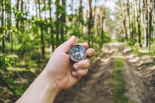 숲의 배경에 남자의 손에 나침반. 관광을 주제로 한 개념입니다.