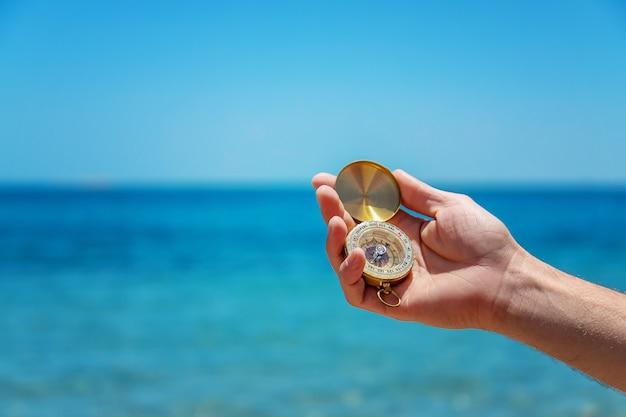 Компас в руке против моря