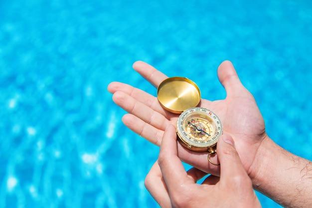 Компас в руках человека на фоне бассейна