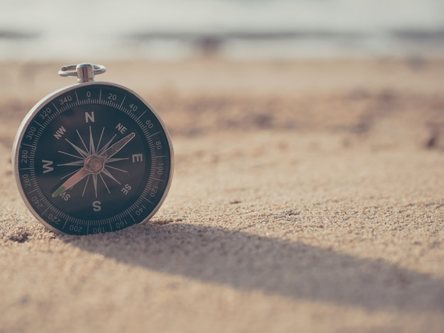 Compass is placed on the beach and sunshine in the evening sunset
