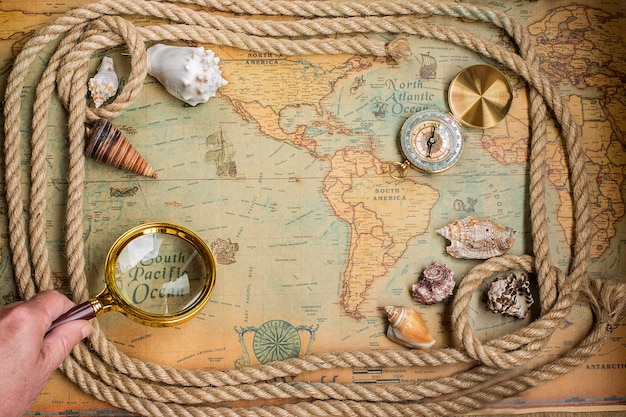 Compass,  magnifier and rope on vintage map