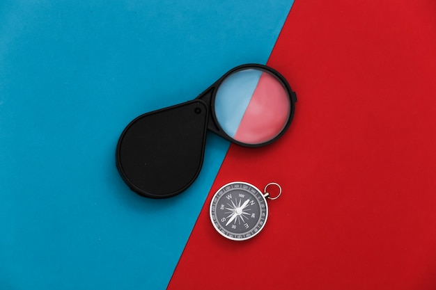 Compass and magnifying glass on red-blue