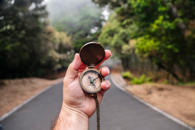 A compass in a man's hand with a road