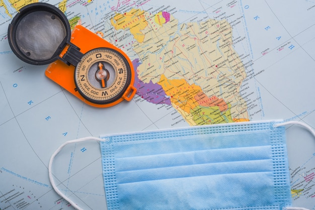 Compass and medical mask over the world map. safe travel concept