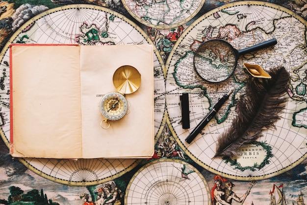 Compass on notebook near writing supplies