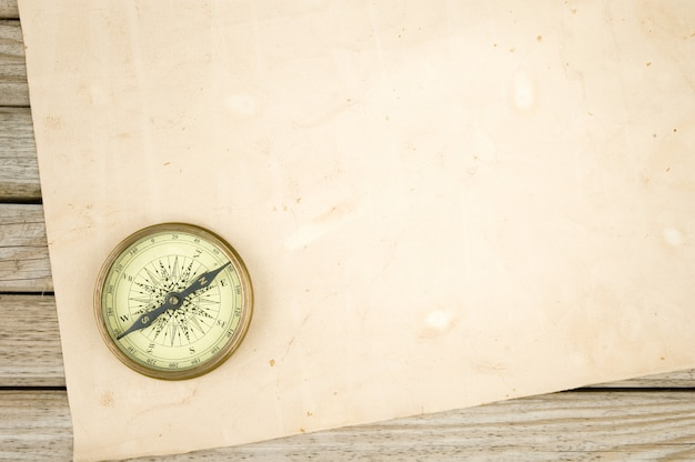 Compass and old paper on wood background