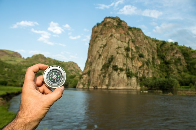 Компас на фоне реки и скал