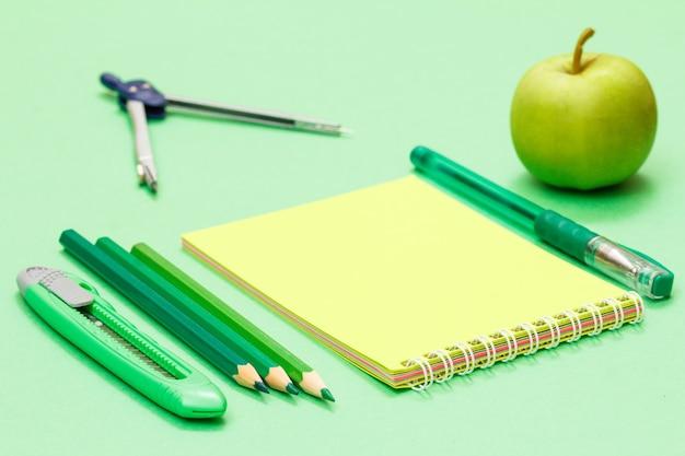 Компас, нож для бумаги, цветные карандаши, блокнот, ручка и яблоко на зеленом фоне. снова в школу концепции. школьные принадлежности. малая глубина резкости.