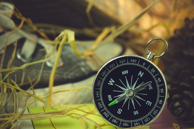 Compass and paper maps with sneakers and pine flowers placed on dry wheat straw in morning sunlight.