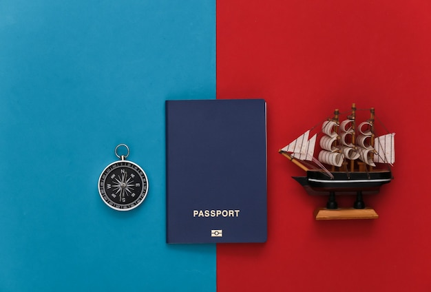 Compass, passport and ship on a red-blue