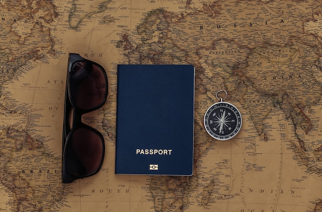 Compass and passport, sunglasses  on old map. travel, adventure concept