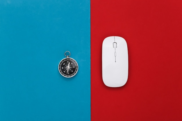 Compass and pc mouse on a red-blue. travel or online business concept