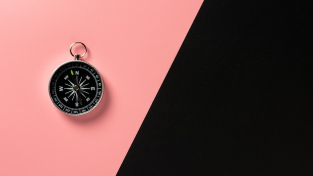 Compass on pink and black paper background.