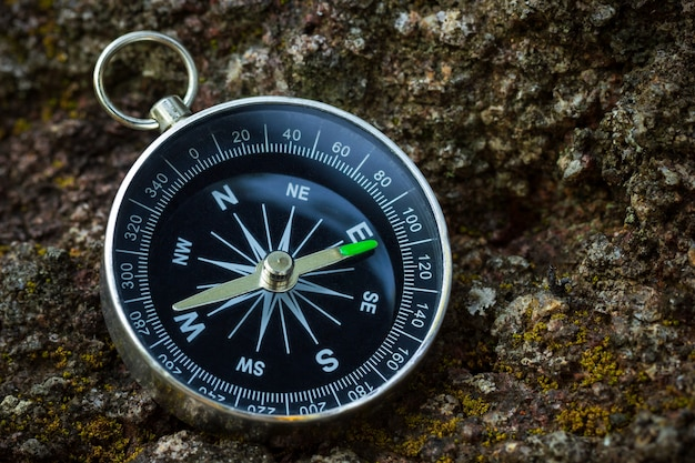 Compass placed on the rock in forest. closeup and copy space. concept of jungle adventure travel.