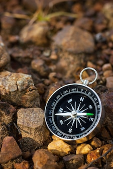 Compass placed on the rock in forest.